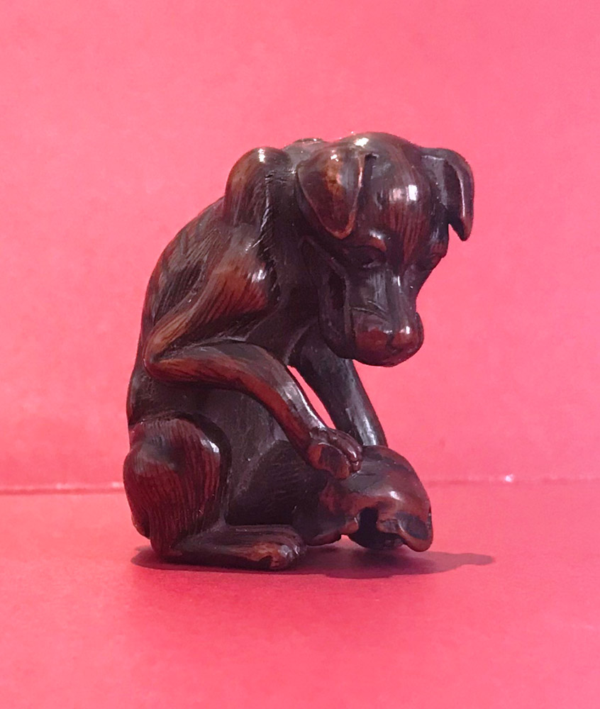 Wood netsuke of a Yama-inu (wild dog) with a skull